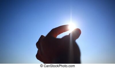 Silhouette of hand and fingers at sunset with ocean background