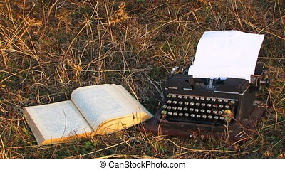 Manual Typewriter And Opened Book On The Grass At Meadow