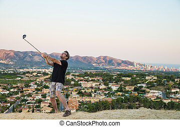 Selfie stick - Guy with selfie stick trying to look cool