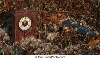 Old Clock And Saw On The Grass With Faded Foliage Covered...