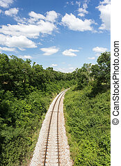 Railway in summer nature. Blue sky with white clouds