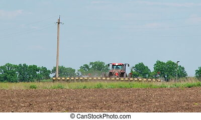 Tractor With Seeder Planting Crops In The Field - One red...