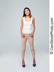 Full length portrait of a casual smiling woman standing over...