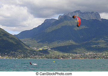 Kitesurf on Annecy lake in France - Man kitesurfing and red...
