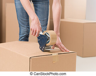 moving house - close-up of female sealing cardboard box with...