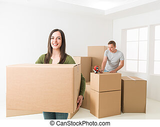 couple moving house - happy young couple packing, preparing...