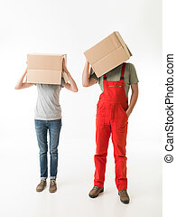 crazy moving day - woman and man standing and holding...