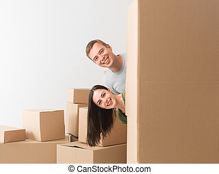 peekaboo - young happy couple hiding behind box, having fun...