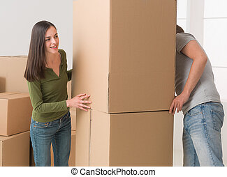 moving house fun - young couple playing hide and seek around...