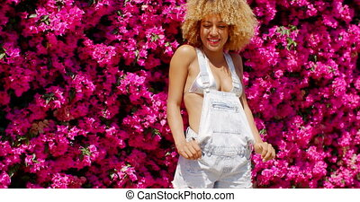 Sexy Girl Posing on Floral Background Behind Her Back She...
