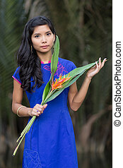 Young Woman in Blue Ao Dai Holding Flowers