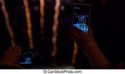 Two Spectators Filming Fireworks Using Smartphones - In the...