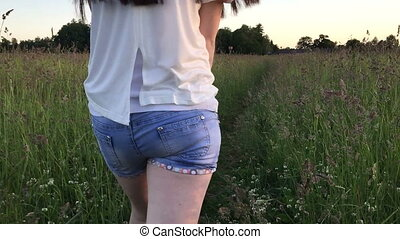Girl in denim shorts goes through the long grass Angle the...
