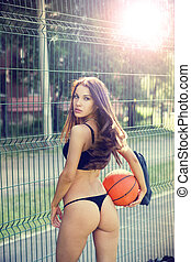 Beautiful young woman with fluttering hair playing basketball outdoors