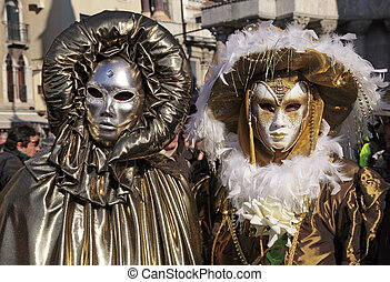 masked persons in golden costume on San Marco Square in...