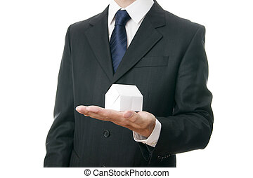 Business man with a paper house in the hand