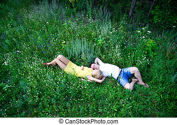 Loving couple lying on green grass in summer