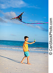 Little boy flying a kite on beach