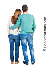 Back view of young embracing couple