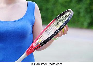 Tennis racket in girl's hand