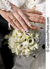 Wedding bouquet and hands with rings.