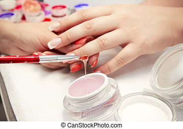 Artificial nails in a beauty salon. Hands close-up. The...