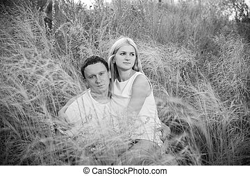 Loving couple on grass in summer. Black and white...