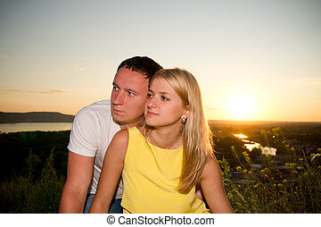 Loving couple at sunset in summer. Young man and woman on...