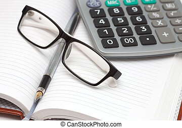 Office items - Notebook, pen, glasses and calculator on the...
