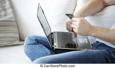 close up of man with laptop and credit card - technology,...