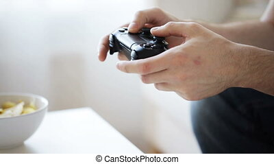 close up of man hands playing video game at home -...