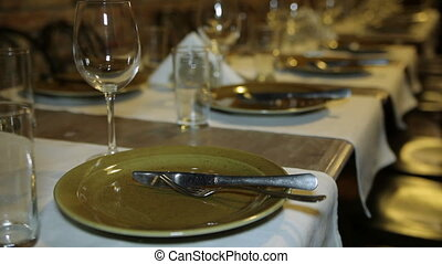 Ancient utensils on a table Glasses, plates and napkins are...