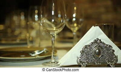 Ancient utensils on a table. Glasses, plates and napkins are...
