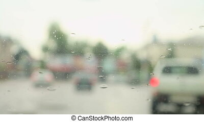 Close-up of raindrops on the windshield of the car.