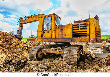 Excavator on the construction site beneath blue cloudy sky