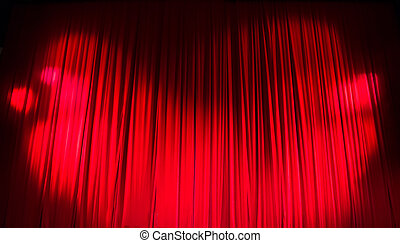 Red closed curtain with light spots in a theater
