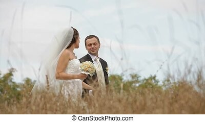 Newly Weds In A Field - Newly weds walking across a field