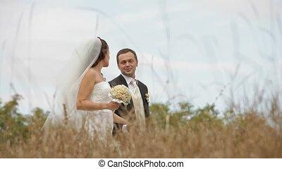 Newly Weds In A Field - Newly weds walking across a field
