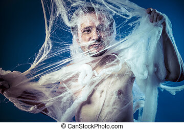 naked man trapped in a huge spider web