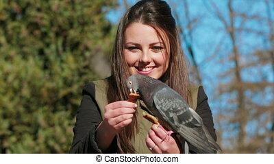 Happy Girl Is Feeding Pigeon - Happy girl is feeding a...