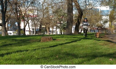 Young Girl Jogging In Park With Dog