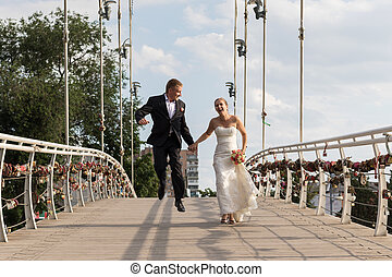 Newlyweds running on the bridge - Bride and groom have fun...