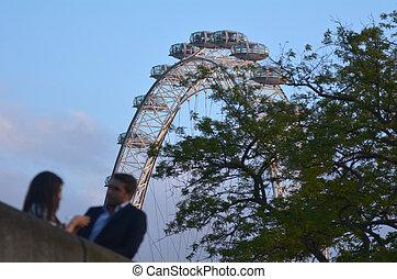Romantic couple under London Eye in London, UK - LONDON, UK...