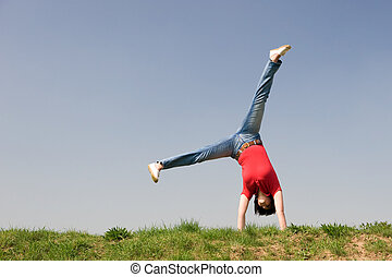 Feel happy - Young woman is turning a cartwheel