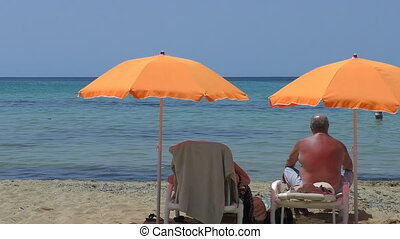 Senior couple under beach umbrellas - An elderly couple...