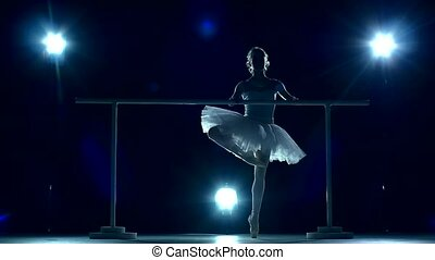 Ballerina standing near a wooden wall on pointe, slow motion...