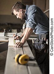 Young carpenter at work - Vertical view of young carpenter...