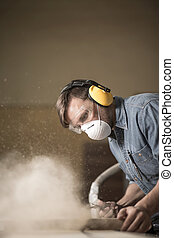 Carpenter using electric saw - Carpenter wearing protective...
