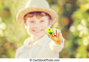 Lucky happy boy in hat holds four leaf clover - Happy boy in...