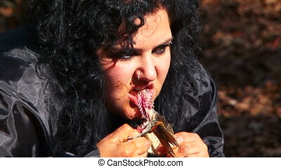 Dark Haired Woman In Black Tearing Dried Fish Apart At Nature